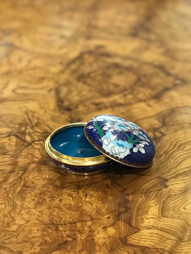 Small, round cloisonné box. This beautiful vintage piece is blue with floral embellishment. Perfect for the vintage collector or an individual looking to achieve that luxurious, high-end look in their home.