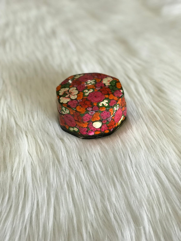 "A vintage, rounded-octagonal, lidded box with hand-painted bright pink, orange, and white floral design and a black, lacquered interior. Triangle-shaped notch closure and small, faded ""Made in India"" sticker on bottom."