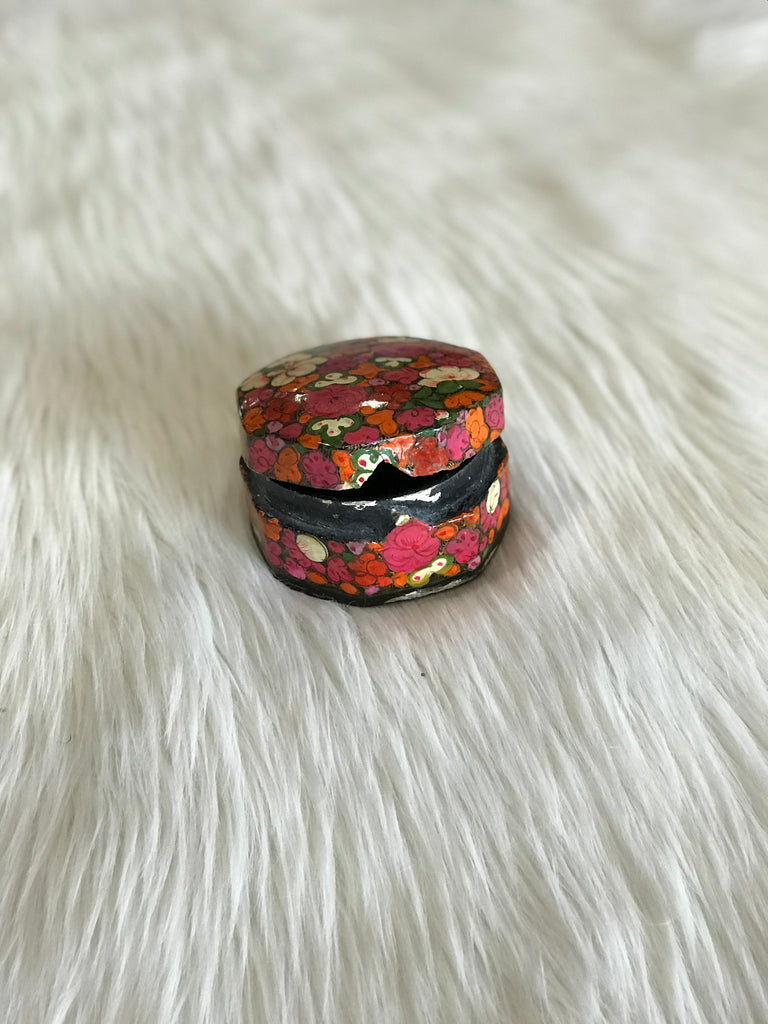 A vintage, rounded-octagonal, lidded box with hand-painted bright pink, orange, and white floral design and a black, lacquered interior. Triangle-shaped notch closure shown here