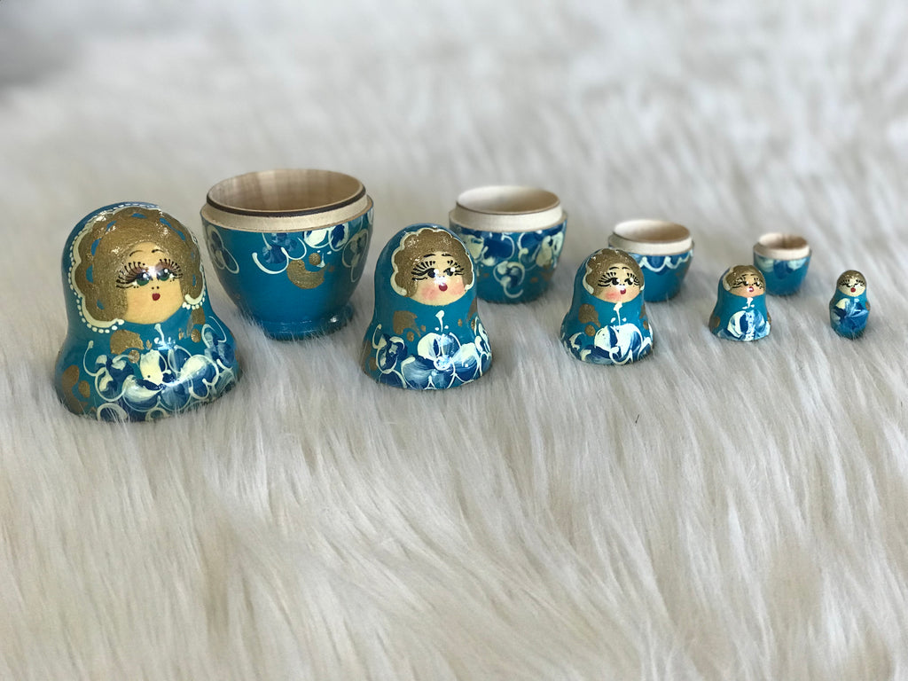 "The sweetest set of 5 bright blue wooden Russian ""Matryoshka"" nesting dolls with gold, white, and blue hand-painted faces and floral detail. Largest doll measures just 3.5"" tall and 2"" wide. Faded ""Made in Russia"" sticker on bottom"""