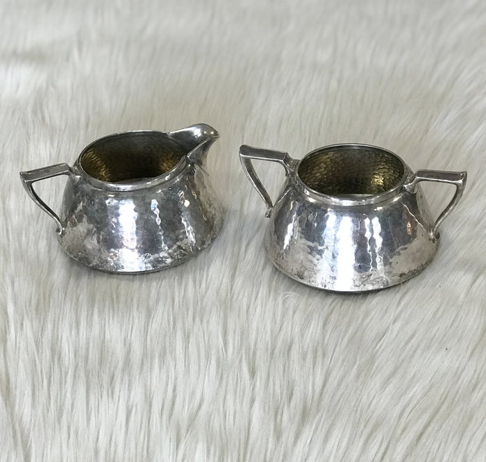 An antique set of Forbes Silver Co. silver-plated, hammered finish sugar bowl and creamer circa 1895.