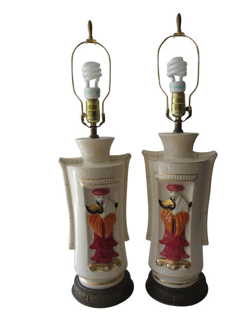A stunning pair of white ceramic lamps with bright, painted pink and orange oriental figures circa 1950. So unique and perfect for the vintage collector or an individual looking to achieve that luxurious, high-end look in their home.
