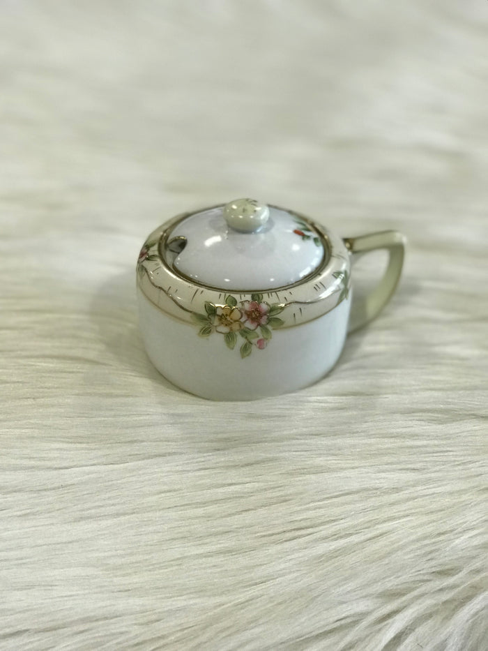 A vintage, lidded Nippon porcelain sugar bowl with hand-painted pink, yellow, green, and gold floral detailing.