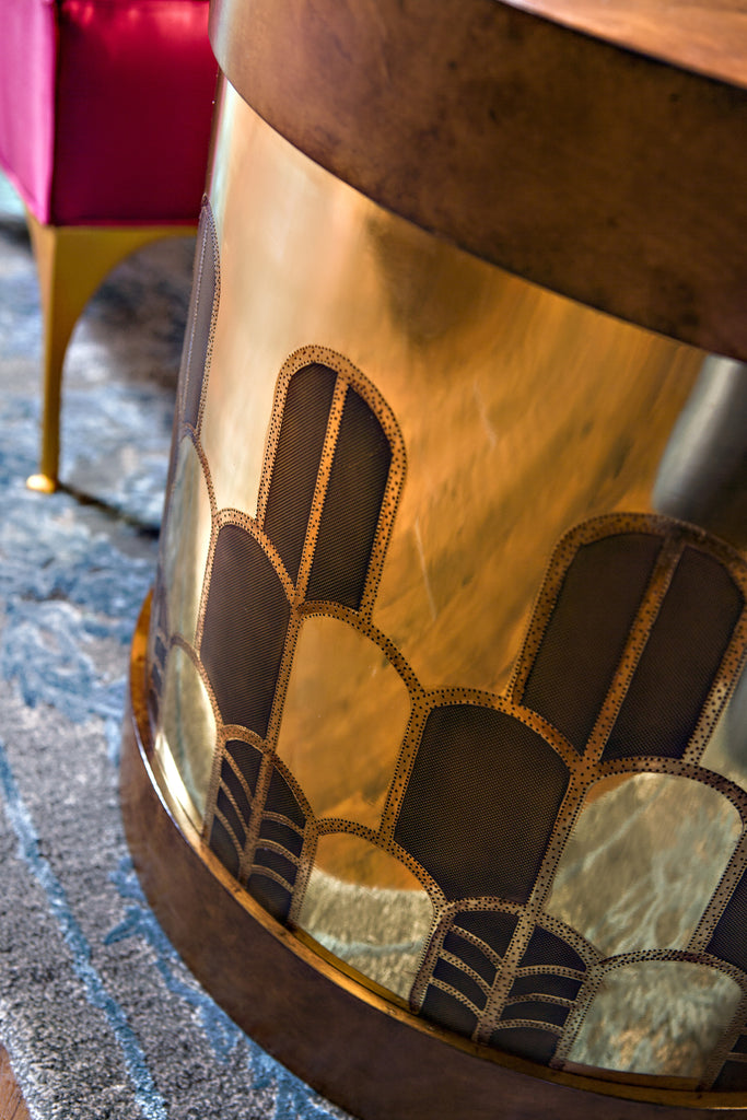 The Gibson Side Table has a hatbox-inspired form and is beautifully hand-etched in Deco design on brass or copper. The top and base are finished in burl, rosewood or lacquer. This piece from The Facet Collection was designed by Michelle Workman for French Heritage and is perfect for anyone looking to achieve that luxurious, high-end look in their home. Detail shot of the midtone Burl and brass finish option shown here.