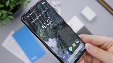 Android phone with cracked screen in hand