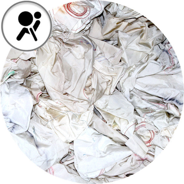 A round cut image of many white Airbags. In the left corner of the picture is an icon that symbolizes airbags