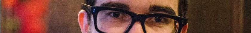 A detail shot of the eyes of a young man with glasses