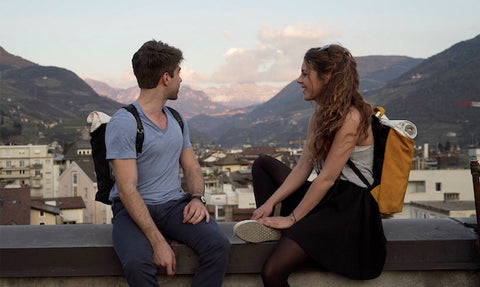 A girl wearing a yellow Airpaq and a guy wearing a black one sitting on the balustrade of a roof top. In the background is the city and mountain panorama of Bolzano.