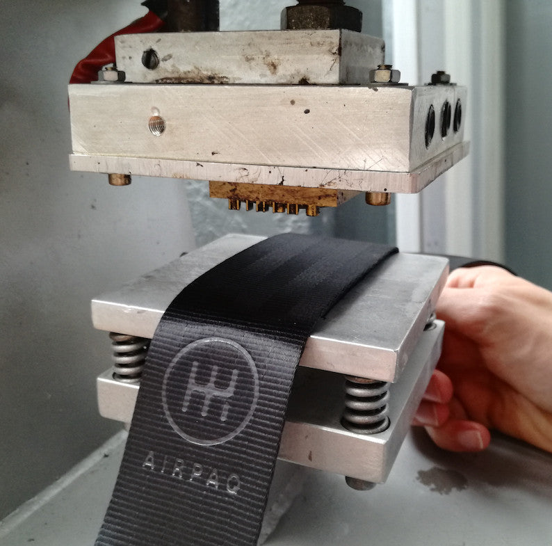 A close up on the process of branding the Airpaq logo on a seat belt