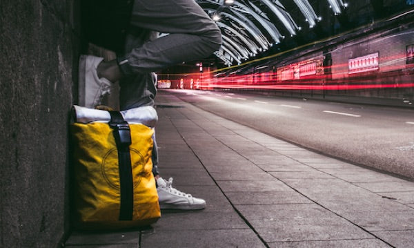 A yellow Airpaq under a bridge with a person standing next to it. Car lights are captured too.