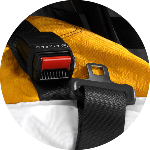 close up on the closing mechanism of the airpaq. Yellow backpack that is closed using a car buckle and clicker