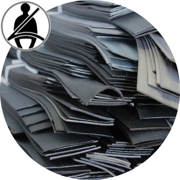 A round cut image of a pile of cut seat belt pieces that are used to produce the back of the Airpaq. In the left corner of the picture is an icon that symbolizes seat belts