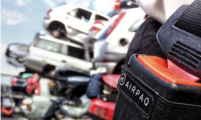 A black Airpaq hanged in the opened engine hood of a red scrapped car