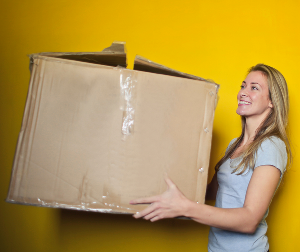 woman holding a large cardboard box with yellow wall background