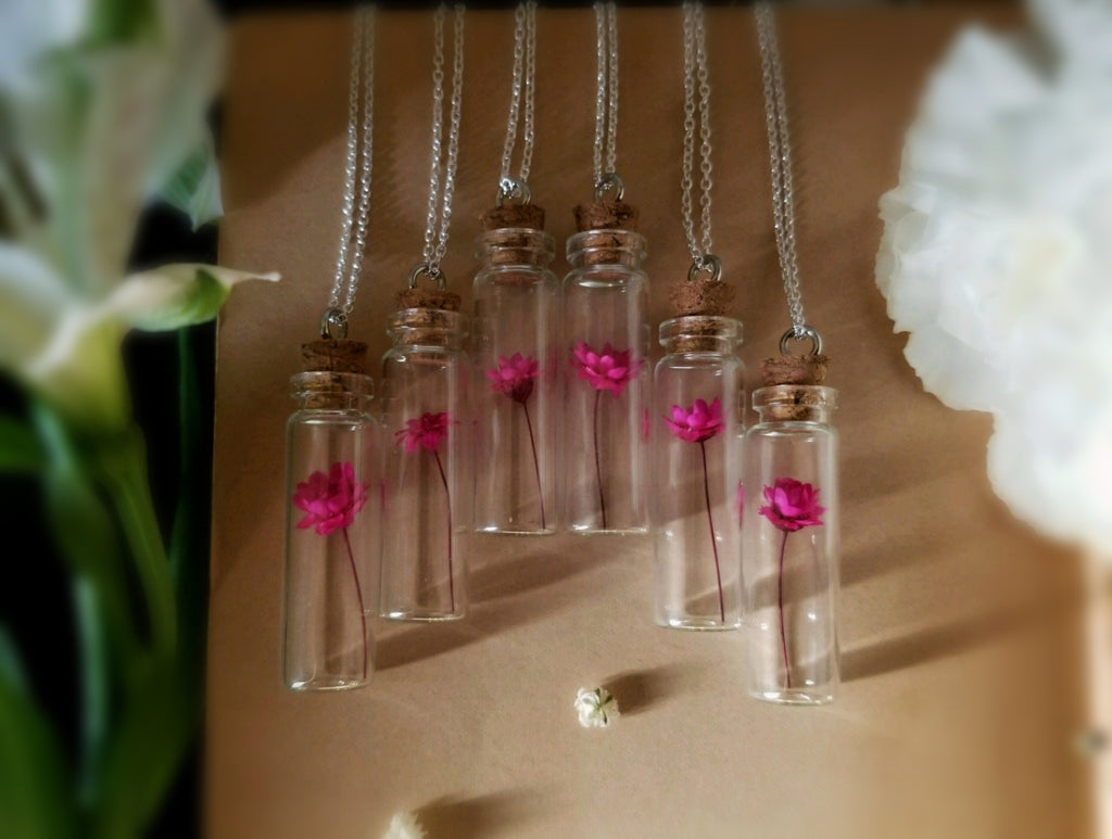 Pink strawflower enclosed in a glass vial strung onto silver chain