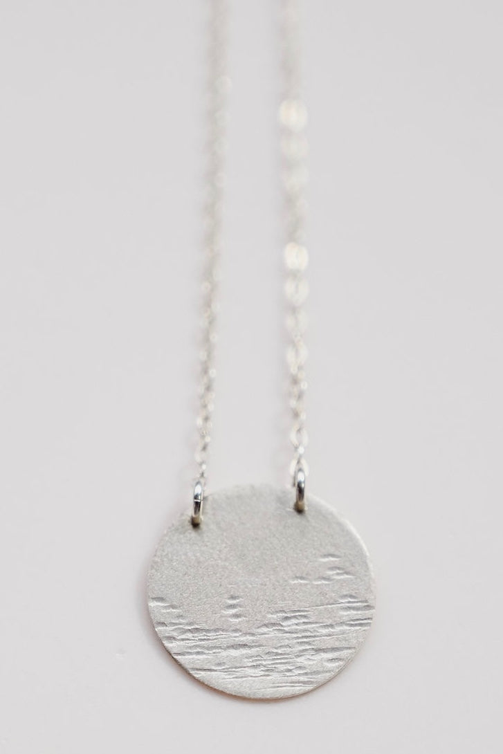 A closeup up of the moon over water silver necklace
