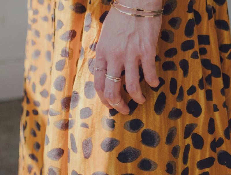 A model wearing the gold orbit meditation ring with gemstone on her middle finger