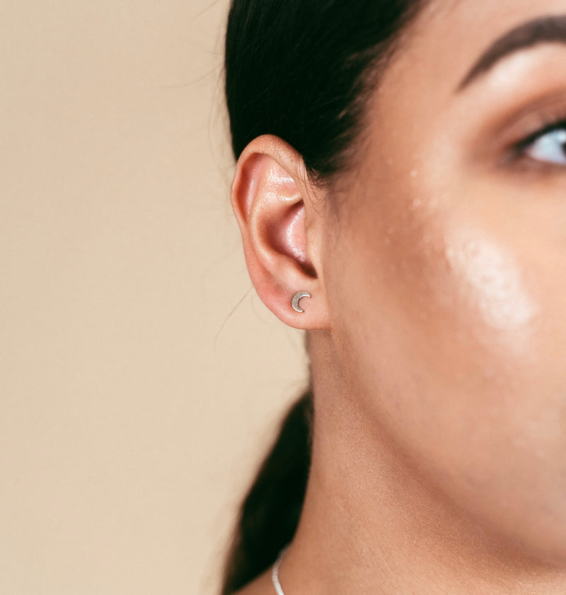 a closeup shot of our model wearing the gold crescent moon studs