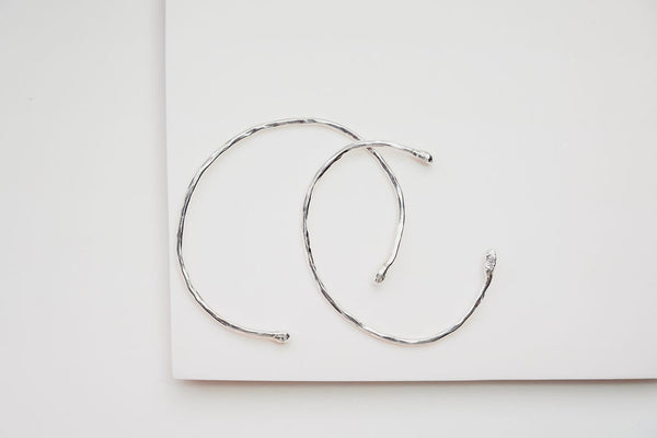 An overhead view of two silver branch cuffs