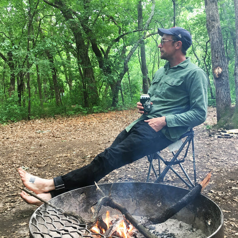 Canoe Club Father Interview Ben drinking Miller Lite Wearing Orslow, Railcar, and Knickerbocker while sitting by a campfire in Wisconsin