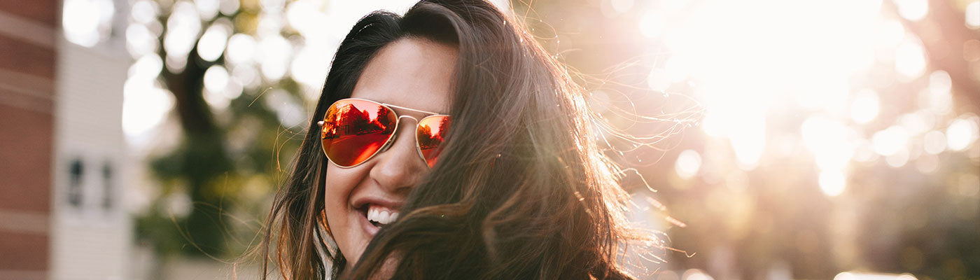 Girl wearing sunglasses with sun shining in the background