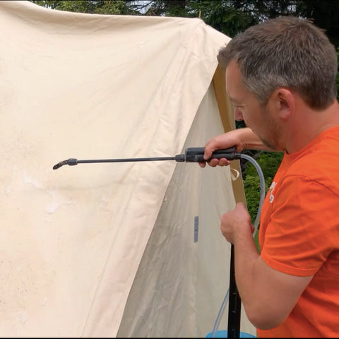Man spraying canvas bell tent