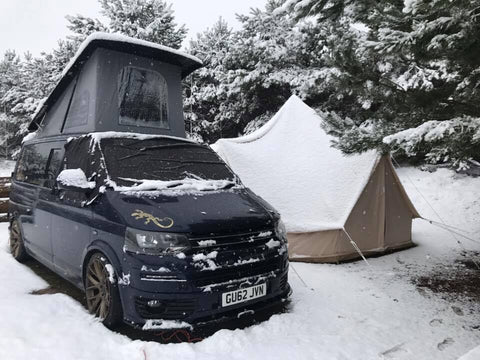 Black T6 VW Camper van attached to glawning in the snow