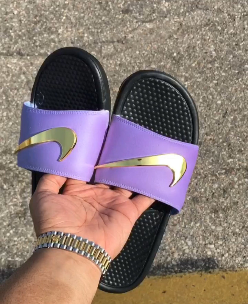 purple nike flip flops with gold check