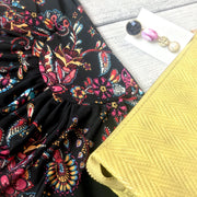 Close up image of black wrap dress with red floral pattern and yellow purse - 9Lilas