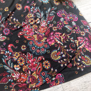 Close up image of the skirt of a black wrap dress with red floral pattern - 9Lilas