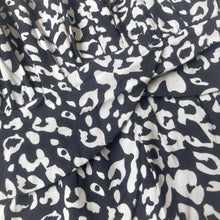 Close up image of a black romper with white leopard spots - 9Lilas