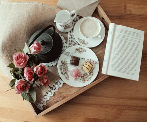 A teacup of coffee with cake, pink roses and a book on wooden tray