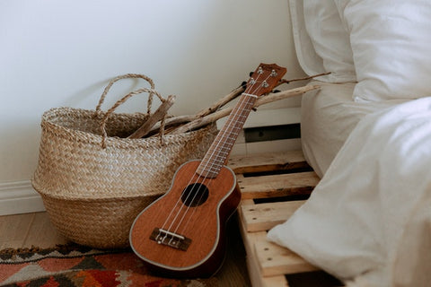 bed beside a small guitar and basket