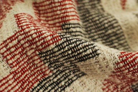 close-up of a white, red and black rug