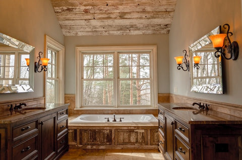 comfort room with white bathtub and brown cabinets