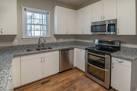kitchen with white cabinets, sink, oven