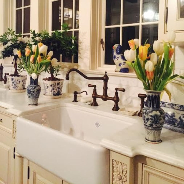 shaws original farmhouse sink with flowers in kitchen