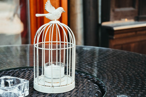 small white birdcage with candle inside