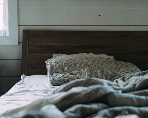 unmade bed with one pillow and wooden headboard