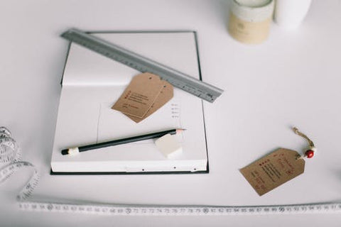 white tape measure, pencil and notebook