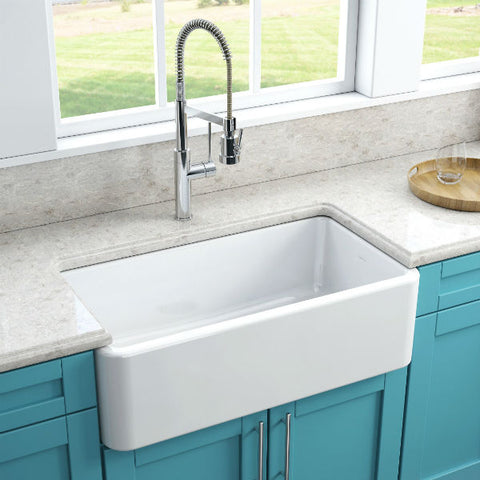 Image of Latoscana LFS3318W White Fireclay Farmhouse Sink smooth side installed with blue cabinets