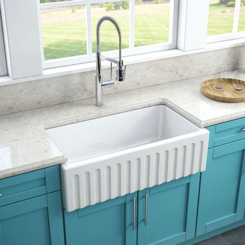 Image of Latoscana LFS3318W White Fireclay Farmhouse Sink fluted design installed with blue cabinet