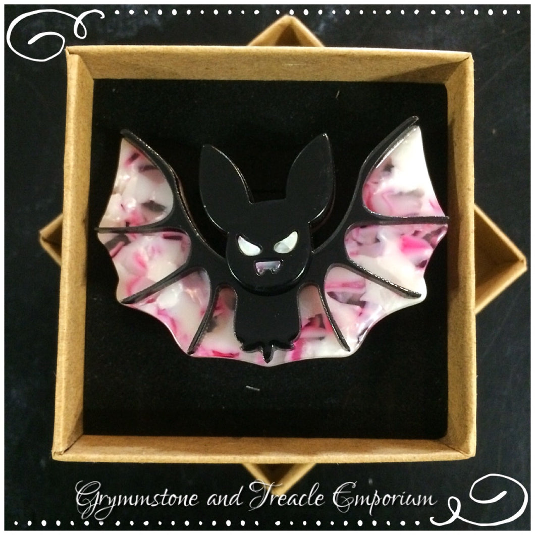 Celluloid brooch in the shape of an adorable bat with stretched wings, in pink, white and black
