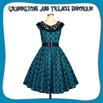fifties style dress in blue teal with black pattern, neckline has black embroidery and includes a black buckled belt