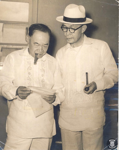 Laurel is on the left smoking a cigar and reviewing documents in a jusi (silk) barong. Photo is likely circa early 1950's.
