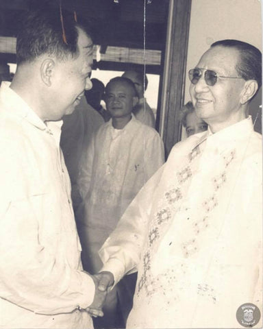 A handshake with President Quirino who is on the right wearing a barong.