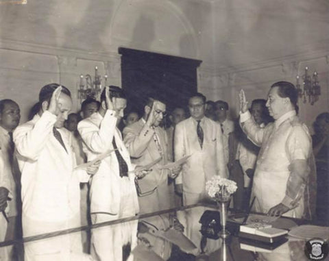 President Quirino (right) wears a barong during an oath-taking ceremony for new officers at Malacañang Palace