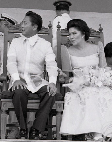 President Marcos and First Lady Imelda sit at Clark Air Force Base for turnover ceremonies on 14 March 1979. Marcos wears a Pierre Cardin Barong Tagalog.