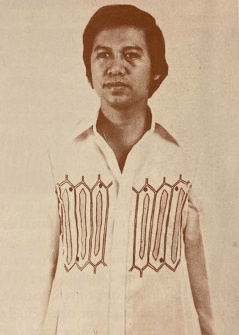 Evaristo wears a Barong Tagalog with an op art pattern going across the top part of the torso