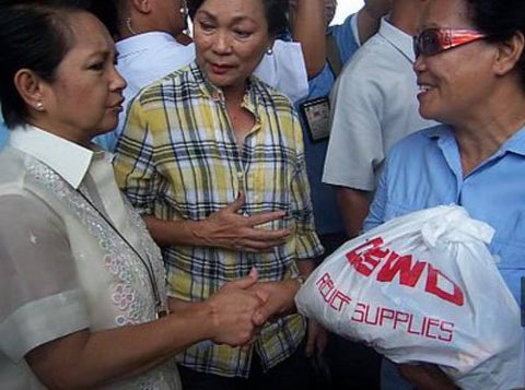 Arroyo in a barong while distributing relief goods during Typhoon Frank